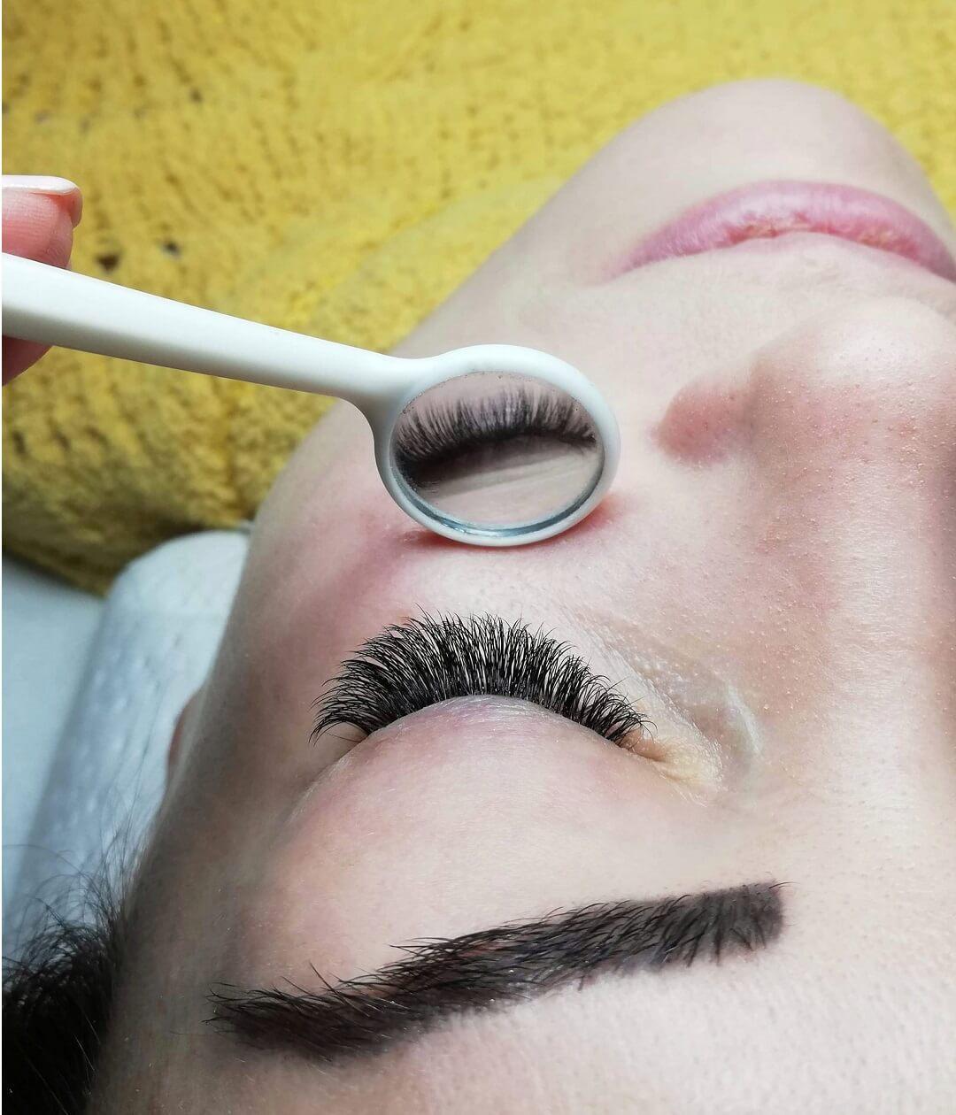 Przedłużanie rzęs warszawa widok twarzy oraz małego białego lusterka, który pokazuje efekt pracy kosmetyczki
